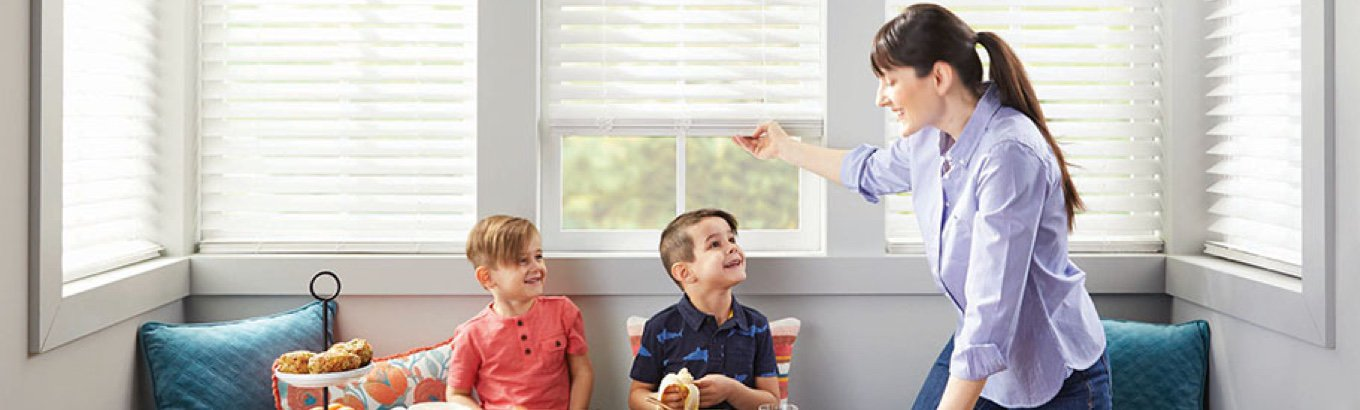 A mother lifting cordless blinds at the breakfast table. Starts the post for how to measure for blinds and shades on Walmart.