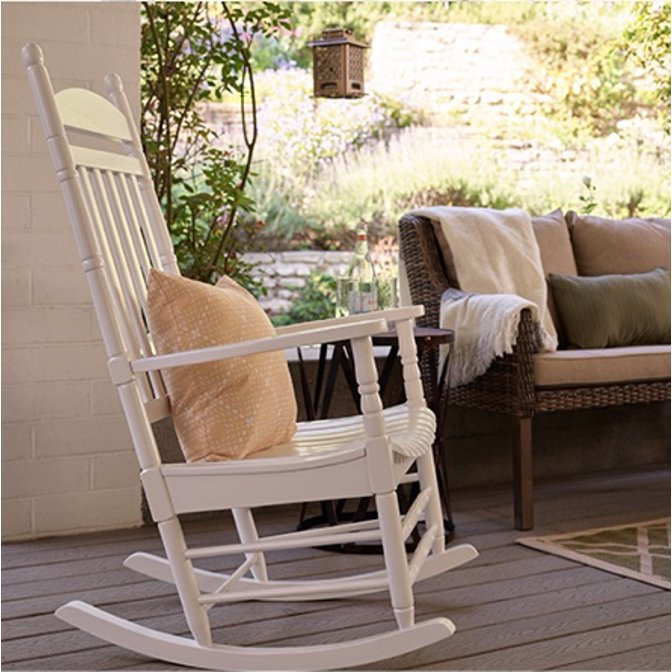 A white rocking chair next to a sofa on a front porch.