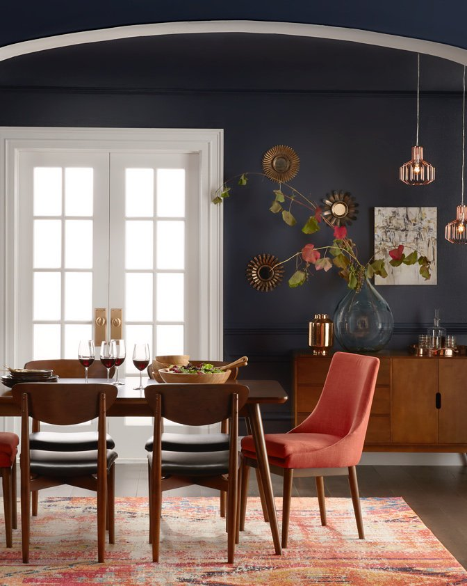 A mid-century modern dining room with Danish modern dining chairs, an upholstered end chair, a stylish buffet and statement area rug in the dining room.