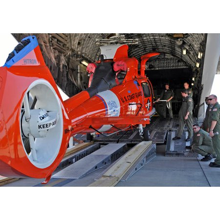 An aircrew loads a Coast Guard HH-65 Dolphin helicopter onto a C-17 Globemaster III Poster Print by Stocktrek Images