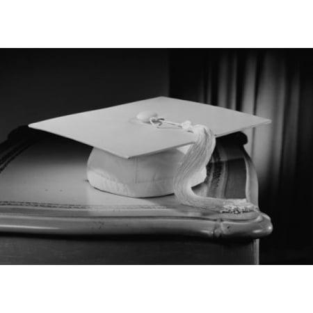Graduation mortar board on bedside table Poster Print (24 x 36)