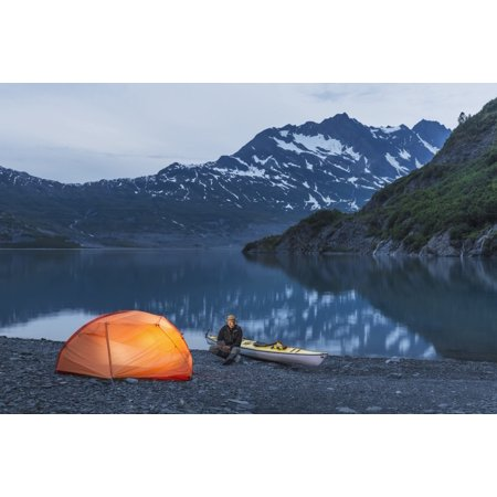 Man reading on a electronic tablet while camping with a tent and kayak at Shoup Bay State Marine Park Prince William sound Valdez Southcentral Alaska Stretched Canvas - Kevin Smith  Design Pics (19 x