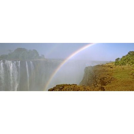 Rainbow form in the spray created by the water cascading over the Victoria Falls Zimbabwe Canvas Art - Panoramic Images (18 x 7)