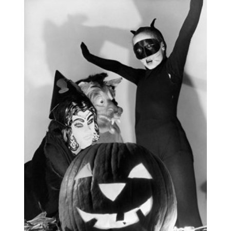 Close-up of an illuminated jack o lantern with three people wearing Halloween costumes behind it Poster Print