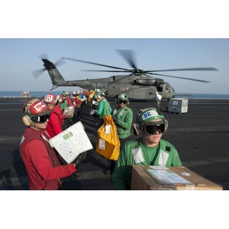 Arabian Gulf December 19 2013 - Sailors unload mail from an MH-53E Sea Dragon helicopter on the flight deck of the aircraft carrier USS Harry S Truman Poster Print