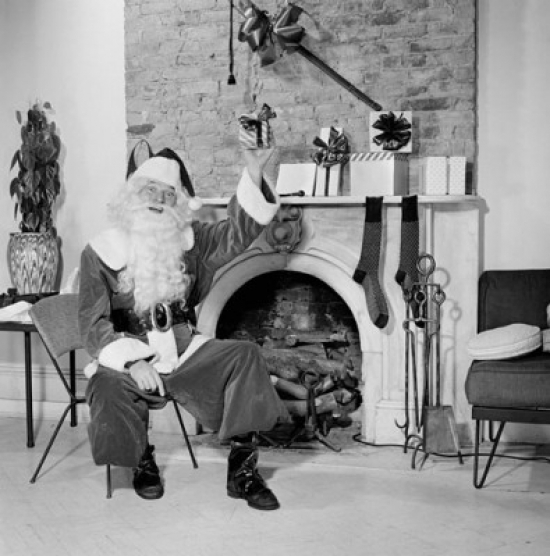 Portrait of Santa Claus sitting in front of a fireplace and holding