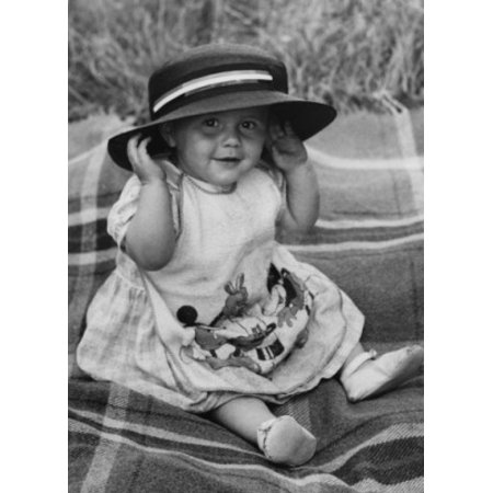 Baby girl sitting on blanket smiling and wearing hat Canvas Art - (24 x 36)