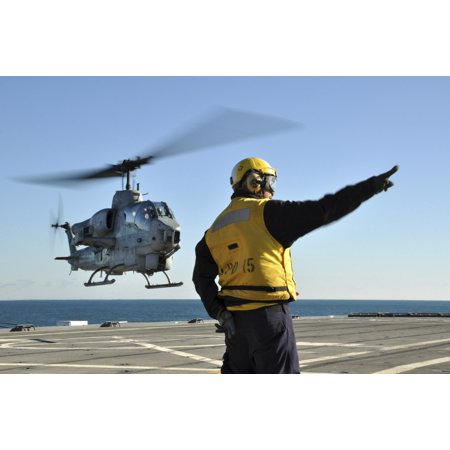 Atlantic Ocean November 30 2011 - Aviation Boatswains Mate Airman directs an AH-1W Super Cobra helicopter as it lifts off from the amphibious transport dock ship USS Ponce Poster Print