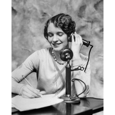 - 1920s Smiling Woman Sitting At Desk Writing And Talking On Candlestick Telephone Print By Vintage Collection