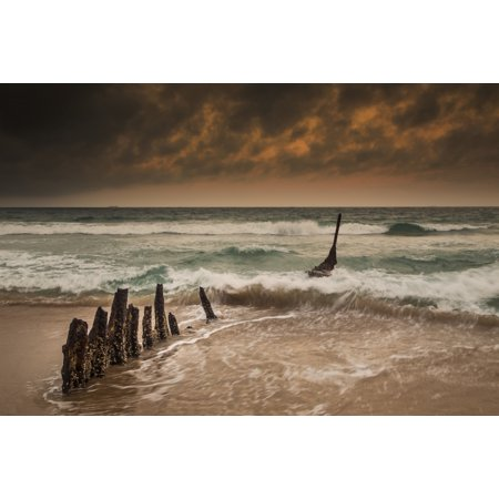 Wooden posts on a beach with a boat being tossed in the water and waves crashing into the sand under a cloudy sky Queensland Australia Canvas Art - John Short  Design Pics (38 x 24) ()
