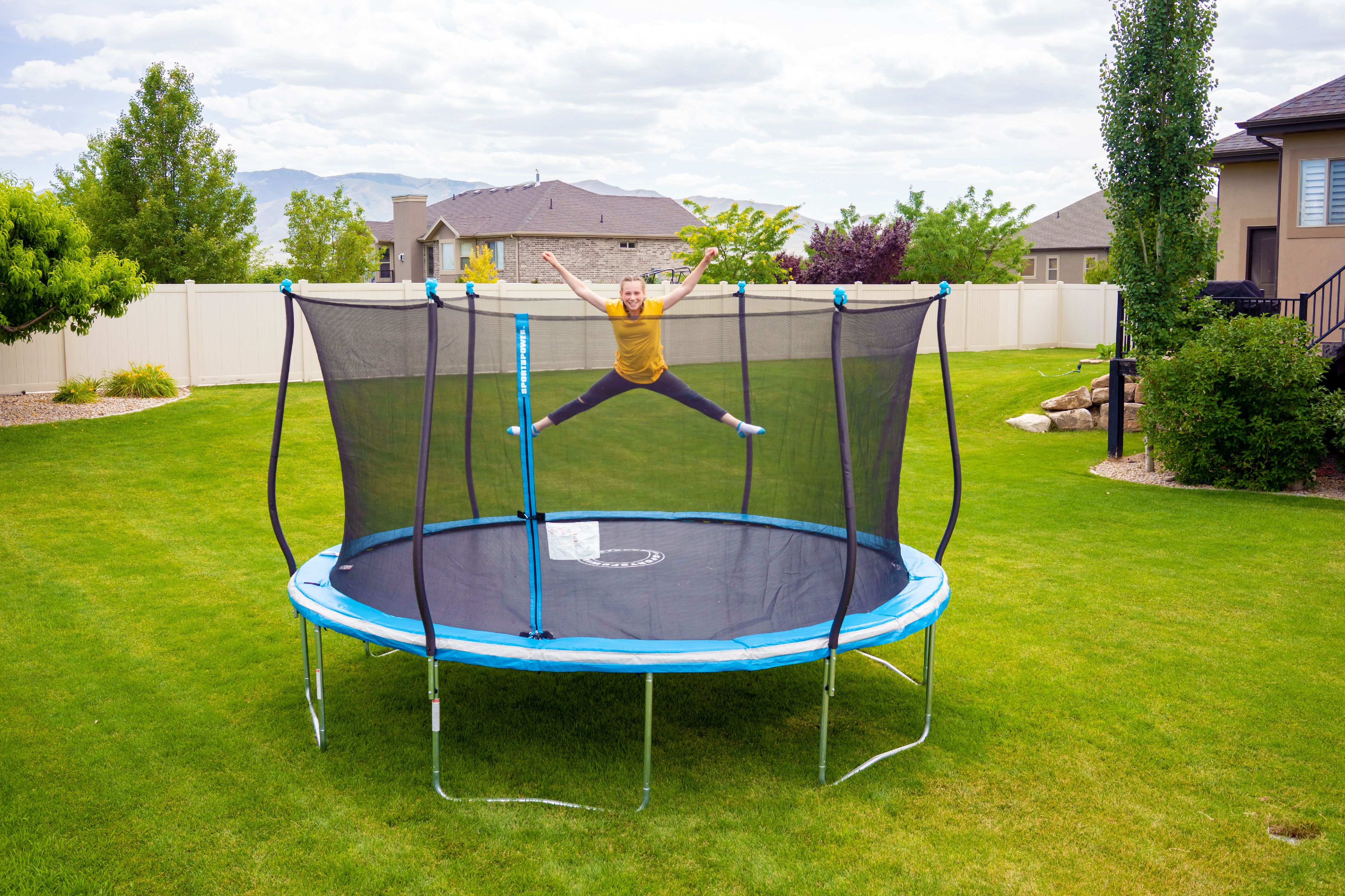 Bouncing on a trampoline in an open area.