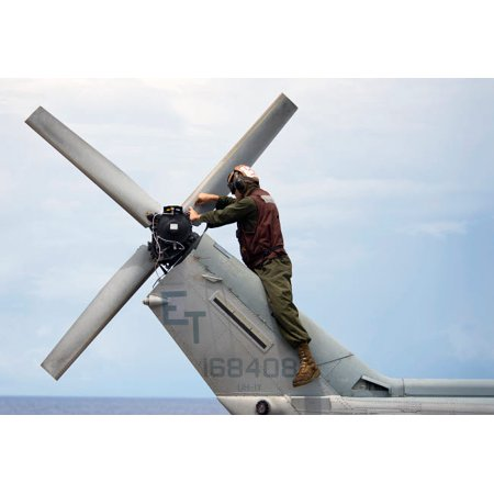 A Marine conducts maintenance on the tail of an UH-1N Huey helicopter Poster Print by Stocktrek Images