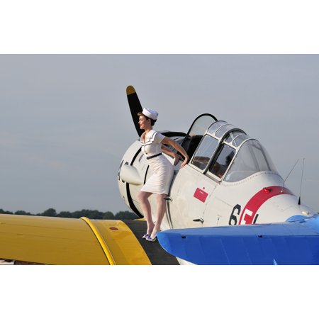 Beautiful 1940s style pin-up girl in retro attire sitting on the wing of a vintage T-6 Texan aircraft Poster Print