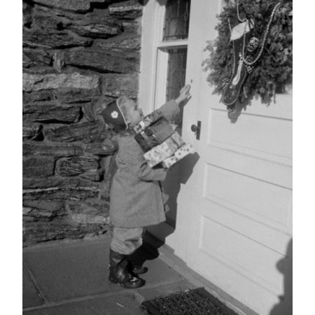 Girl carrying Christmas gifts and ringing door bell Poster Print (18 x 24)