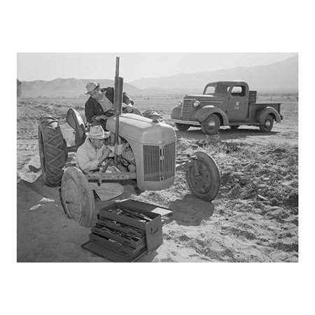 Mechanic repairs tractor engine while driver looks on tool box in the foreground pick-up truck in the background  Ansel Easton Adams was an American photographer best known for his black-and-white