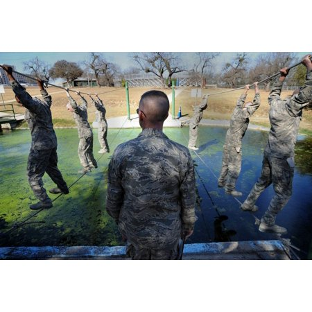 LAMINATED POSTER At the obstacle course at Lackland Air Force Base, Texas, basic trainees are watched by a military t Poster Print 24 x