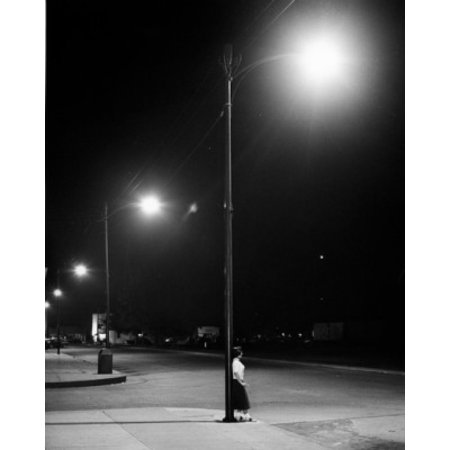 Woman leaning on lamp post in street Stretched Canvas -  (24 x 36) ()