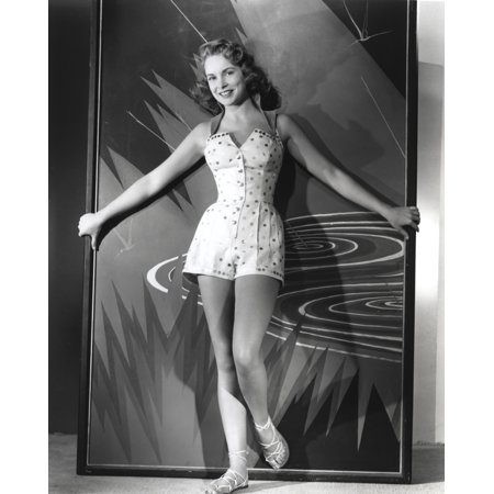 Janet Leigh Posed in White Polka Dot Corset Short Dress with Hands Spread to the Side Holding a Framed Abstract Painting Photo Print