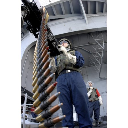 Gunners Mate Seaman taking aim on a 50-caliber machine gun at a floating target aboard USS Ronald Reagan Print