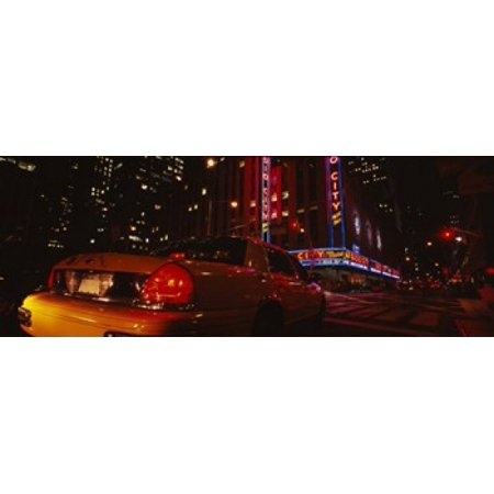 Rockefeller Center Radio City Music Hall (Car on a road Radio City Music Hall Rockefeller Center Manhattan New York City New York State USA Poster Print )