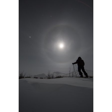 Man snowshoeing along the Dempster Highway under a moon glowing with rings Yukon Canada Canvas Art - Robert Postma Design Pics (24 x 38)