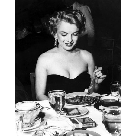 Marilyn Monroe sitting at a dining table Photo