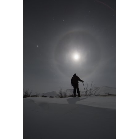 Man snowshoeing along the Dempster Highway under a moon glowing with rings Yukon Canada Canvas Art - Robert Postma Design Pics (12 x 19)