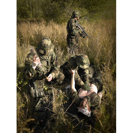 US Navy SEALs give first aid to a wounded soldier Poster Print