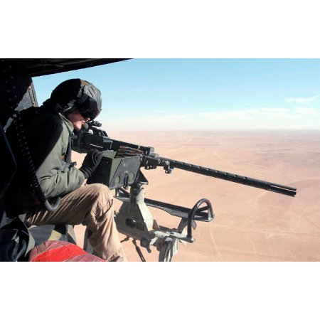 US Marine checks out the GAU-16A Cal 50 machine gun onboard his UH-1N Huey helicopter Poster Print by Stocktrek Images