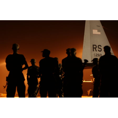 Rwandan soldiers are bathed in the lights of the flight line as they line up to board a U.S. Air For Poster Print 24 x 36