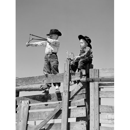 1950s Two Young Boys Dressed As Cowboys Shooting Slingshots On Top Of Wooden Fence Outdoor Print By Vintage - Wooden Slingshots