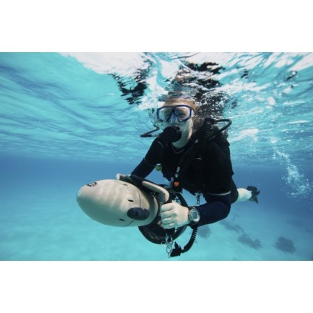 Scuba diver navigates the waters using a diver propulsion vehicle off the coast of Bonaire Caribbean Netherlands Poster Print