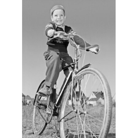 Low angle view of a boy riding a bicycle Poster
