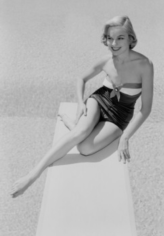 Young woman in swimwear sitting on diving board Poster Print by Superstock
