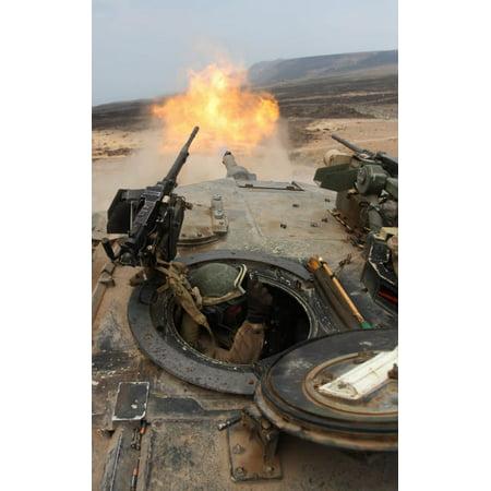A tank crewman braces himself after firing a 120mm round from a M1A1 Abrams battle tank Poster Print by Stocktrek Images