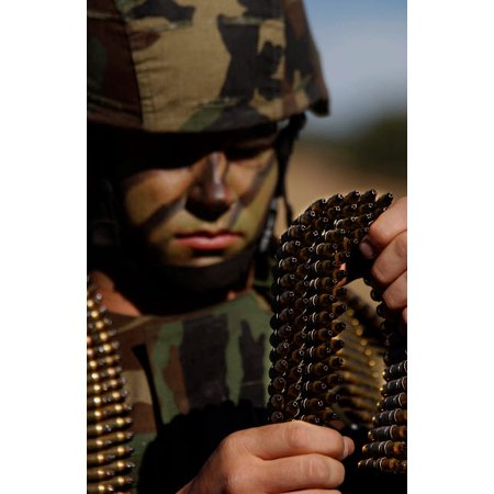 Airman loads up ammunition for the M-249 automatic rifle Poster Print by Stocktrek Images thumbnail
