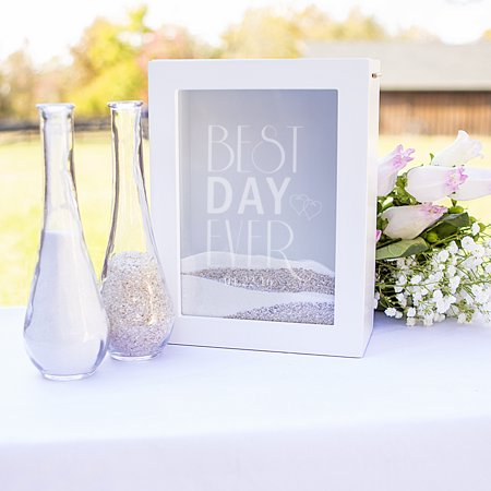 Personalized Best Day Ever 3-Piece Sand Shadow Box Set A modern twist on the original sand unity set is the Personalized Best Day Ever Unity Sand Ceremony Shadow Box Set. Featuring a contemporary shadow box to hold sand and two curvaceous pouring vases, this unity piece is perfect for the best wedding ever. Unite your love into one and after the ceremony, place in your home as a beautiful keepsake. FREE Personalization. Available in two (2) colors Set includes: One (1) large shadow box and two (2) pouring vases. Dimensions: Shadow Box: 6 L. x 3 W. x 8 H. Holds 80 oz. Pouring Vases: 7 L. x 2.2 W. Holds 5.6 oz. each. Features: An enclosed sand shadow box with custom etched glass, two shapely pouring vases, and free personalization. Sand not included. Materials: Glass. Wood. Please note: minor bubbles and swirls are inherent to hand-blown glass. Variations may occur on styles due to their handcrafted nature. Care Instructions: Wipe clean with a damp cloth. Engraving Options: May be engraved with a date (max 8 characters) underneath the Best Day Ever design at no additional cost. Made in China