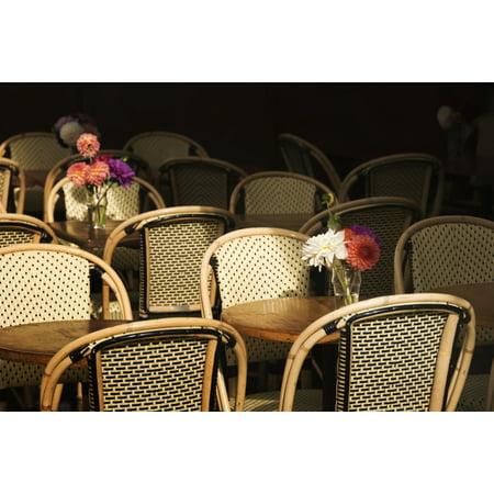 A bouquet of flowers amongst empty parisian bistro chairs and tables Paris France Canvas Art - Philippe Widling  Design Pics (40 x 26) ()