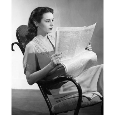 Young woman sitting on a rocking chair reading a newspaper Poster Print