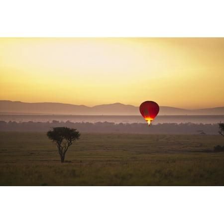 A Red Hot Air Balloon Takes Flight Against The Glowing Sky At Sunset Masai Mara Kenya PosterPrint