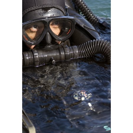 A Navy SEAL combat swimmer diving a oxygen rebreather taking a quick sneak and peak above the waterline to ensure he is on course to the target Poster Print