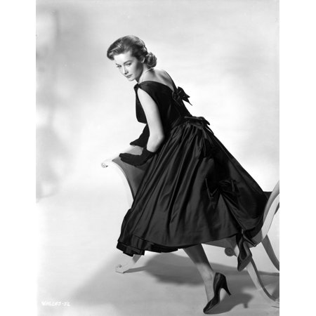 Vera Miles kneeling onto a chaise lounger looking behind her shoulder wearing a black sleeveless gown with bows elegantly placed along the back Photo Print