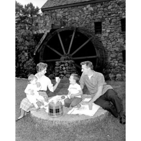 Family with baby girl and boy on picnic by water mill Canvas Art - (24 x 36)