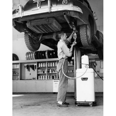 Mid adult man repairing a car in an auto repair shop Poster Print for $<!---->