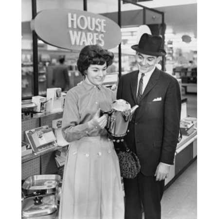 Mid adult woman and a mature man looking at a kettle in a store Poster (Man Woman Store)
