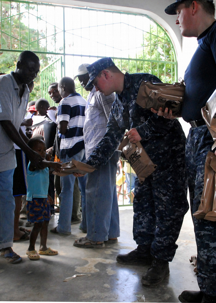 Click here to buy LAMINATED POSTER A Haitian boy receives a (MRE) from Sailors assigned to the dock-landing ship USS Carter Hall (LSD Poster Print 24 x 36 by Home Comforts.