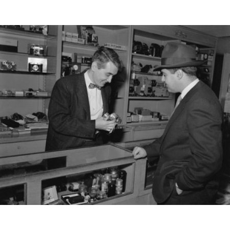 Salesman showing a camera to a customer in a store Poster Print