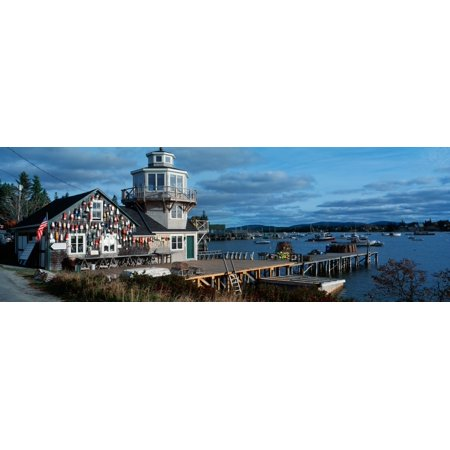 This is a lobster village in New England There is a long pier with lobster traps stacked up at the end It is the southwest harbor with a large fishing house with a tower There are fishing buoys attach