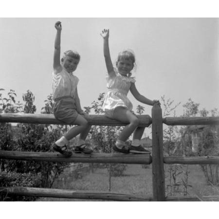 Boy and girl seating on split rail fence waving Poster Print