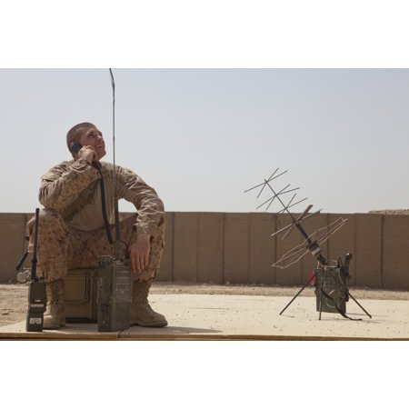 US Marine looks up to the sky while using satellite tactical communications equipment Poster Print